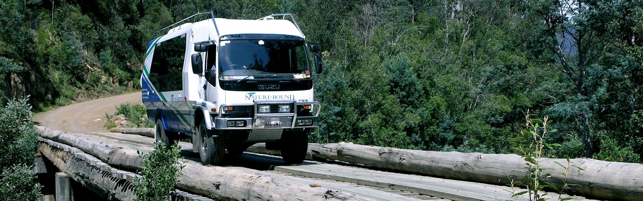 Tour Transport our bus crossing bridge into Tasmanian forests