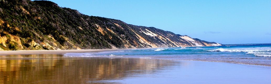 Coloured Sands and ocean beach of Fraser Island featured on our Uniquely Australia Land of Contrasts Tour